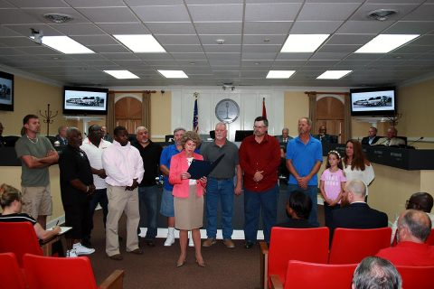Clarksville Mayor Kim McMillan reads the proclamation honoring Screaming Eagle Ready Mix drivers for shielding mourners at a Fort Campbell memorial service from an out-of-town protest group.