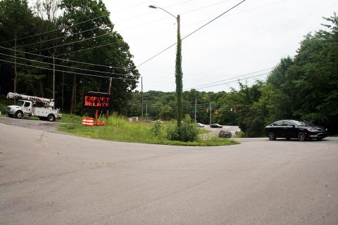 This view east of the intersection of Warfield Boulevard and Dunbar Cave Road shows the early signs of road construction to come: A truck ready for utility relocation work, a warning sign and the busy intersection.