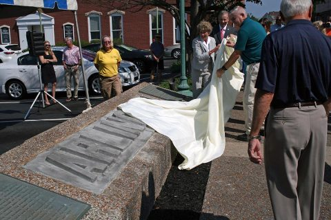 Clarksville Mayor Kim McMillan, Joe Pitts of Planters Bank, and Kurt Bryant of the County Historical Society helped unveil the newly restored Arlington Hotel monument on Second Street in Downtown Clarksville.