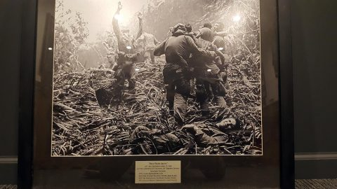 "A copy of ""Help From Above"", which hangs in the headquarters of 2nd Battalion, 327th Infantry Regiment, 101st Airborne Division(Air Assault). The photo was donated by Art Greenspon to the 101st when he was inducted as an honorary member of the 327th Infantry Regiment in 2014. Greenspon identified the names and positions of the Soldiers in the photo. Sgt. Maj Watson Baldwin stands with his hands raised signaling to a helicopter. Spc. 4 Dallas Brown lays on the ground grimacing in pain. Sgt. Tim Wintenburg, helmetless on the far right, glances back at the camera. (Original Photo by Art Greenspon, Associated Press, April, 1968. U.S Army Photo by 1st Lt. Daniel Johnson)"
