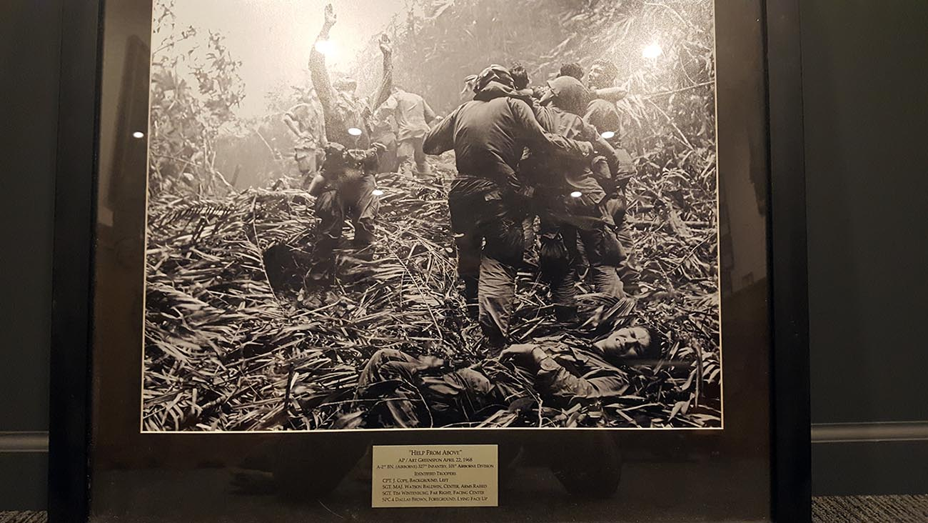 """A copy of """"Help From Above"""", which hangs in the headquarters of 2nd Battalion, 327th Infantry Regiment, 101st Airborne Division(Air Assault). The photo was donated by Art Greenspon to the 101st when he was inducted as an honorary member of the 327th Infantry Regiment in 2014. Greenspon identified the names and positions of the Soldiers in the photo. Sgt. Maj Watson Baldwin stands with his hands raised signaling to a helicopter. Spc. 4 Dallas Brown lays on the ground grimacing in pain. Sgt. Tim Wintenburg, helmetless on the far right, glances back at the camera. (Original Photo by Art Greenspon, Associated Press, April, 1968. U.S Army Photo by 1st Lt. Daniel Johnson)"""