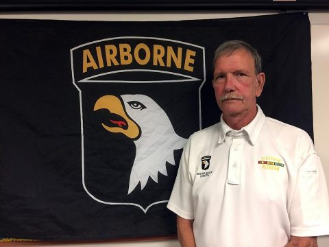 "Dallas Brown, a Vietnam War veteran who served with Company A, 2nd Battalion, 327th Infantry Regiment, 1st Brigade [Separate], 101st Airborne Division poses next to a Screaming Eagle Flag, Aug 8, 2017, at Fort Campbell, Kentucky. Brown, along with Tim Winterburg , Watson Baldwin, and Jay Cope, is one of the Soldiers pictured in the famous Vietnam War photograph ""Help from Above"" by Art Greenspon. When the photo was taken, Brown was laying on the ground grimacing in pain from an injury sustained during a firefight with the NVA. (Sgt. William White)"