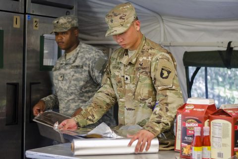 Specialist Johnsid Legaspi, a food service specialist assigned to E Company, 6th Battalion, 101st General Support Aviation Battalion, 101st Combat Aviation Brigade, 101st Airborne Division, helps prepare a lunch featuring fried chicken Aug. 9 at Fort Campbell, Kentucky. Legaspi is part of a 13-member team participating in the Army's premier culinary arts competition, the Philip A. Connelly Program. (Leejay Lockhart, Fort Campbell Public Affairs Office)