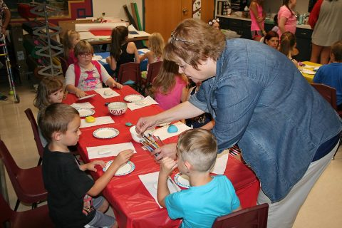Arts for Hearts leader Rita Arancibia assists youngsters at the Public Library as they get ready to paint Kindness Rocks.