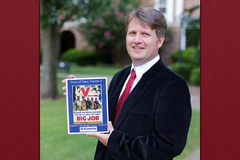 "Austin Peay State University Associate Professor Kevin Tanner holds up a copy of his latest volume release of the book ""Faces of Valor."""