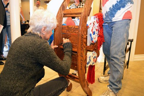 Betty Tidwell, writes a message on the rocking horse honoring her late son Sgt. 1st Class Tony Knier, during a presentation ceremony at the Fort Campbell Fisher House Oct. 13. The rocking horse is meant to bring joy to children staying at the Fisher House, while honoring Knier who was killed in Bayji, Iraq in 2006. The rocking horse is one in a series honoring fallen service members donated to Fisher Houses across the nation. (Maria Yager)