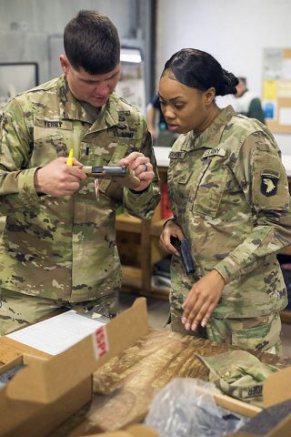 1st Lt. Jon Yerby and Pvt. 1st Class Tia Alexander, C Company, 1st Battalion, 506th Infantry Regiment, 1st Brigade Combat Team, 101st Airborne Division (Air Assault) inspect and inventory an M17 or Modular Handgun System at an installation warehouse, November 27th. (Sgt. Samantha Stoffregen, 101st Airborne Division (Air Assault) Public Affairs)