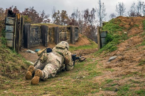 """Sgt. Sa-Voughn Stephens, of Memphis, Tennessee, and a team leader from Company C, 3rd Battalion, 187th Infantry Regiment, 3rd Brigade Combat Team """"Rakkasans"""", low-crawls toward an enemy bunker to clear it by grenade. The enemy bunker was part of a squad live-fire range held by 3-187th Inf. Regt., at Fort Campbell, Ky., Nov. 7. (Spc. Patrick Kirby, 40th Public Affairs Detachment)"""