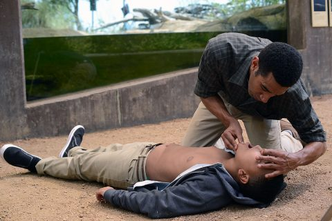 Man administers CPR to child in reenactment illustrating proper technique. (American Heart Association)