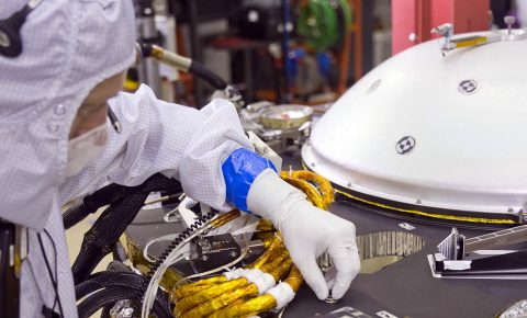 A spacecraft specialist in a clean room at Lockheed Martin Space Systems in Denver, where the InSight lander is being tested, affixes a dime-size chip onto the lander deck in November 2015. A second microchip will be added in 2018. (NASA/JPL Caltech/Lockheed Martin)