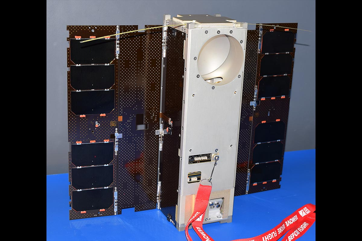 The Microwave Radiometer Technology Acceleration (MiRaTA) satellite, a 3U CubeSat, is shown with solar panels fully deployed, flanking the body of the spacecraft, which has a circular aperture at the top for the microwave radiometer antenna, used for atmospheric science measurements. There are also two small, thin tape-measure antennas on the top, used for UHF radio communication with the ground station. (MIT Lincoln Laboratory)