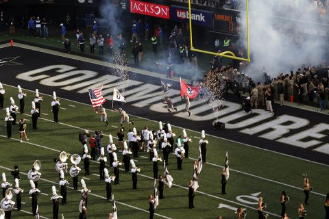 """Vanderbilt University football players run through a tunnel of soldiers of the 2nd Battalion, 32nd Field Artillery Regiment, carrying the U.S. flag, a POW/MIA flag, Tennessee state flag, and the 101st Airborne Division """"Screaming Eagles"""" flag before the University of Kentucky vs. Vanderbilt University football game, Nov. 11. The ceremonies were part of Vanderbilt University's recognition of Veterans Day. (Staff Sgt. Todd Pouliot, 40th Public Affairs Detachment)"""