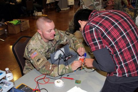 Sgt. 1st Class David Taylor, an electronic maintenance noncommissioned officer with the 101st Airborne Division (Air Assault) Sustainment Brigade, 101st Abn. Div., shows a student the components of a device, Nov. 15, 2017, during Clarksville-Montgomery County School System's annual Eighth-Grade Career Exploration Day at the Wilma Rudolph Event Center in Clarksville, Tennessee. (Spc. Alexes Anderson/101st SBDE Public Affairs)
