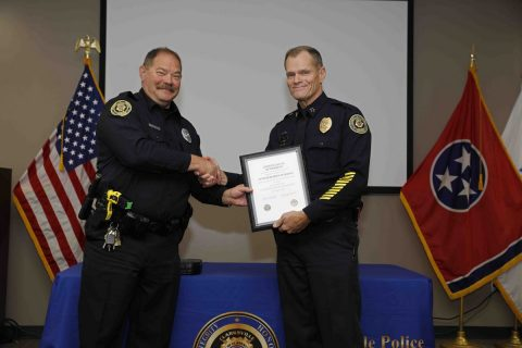 Clarksville Police Chief Al Ansley (left) presents Officer Bob Peterson (right) with a Certificate of Retirement Friday morning during Peterson's retirement ceremony.