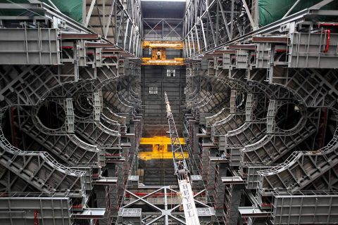 High up in the Vehicle Assembly Building at NASA's Kennedy Space Center in Florida, an overhead crane lowers the final work platform, A north, into place for installation in High Bay 3 on Jan. 12, 2017. (NASA/Frank Michaux)