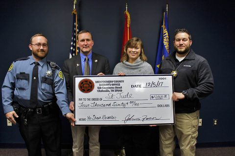 Montgomery County Sheriff John Fuson, Deputy Chad O'Brien, and Investigator Ryan Ayrest present a check to Jackie Proffit with St. Jude's Entertainment Marketing for $4,060.