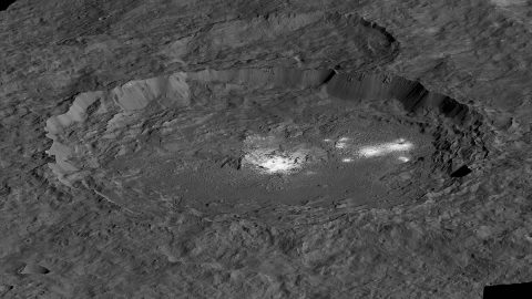 The bright areas of Occator Crater -- Cerealia Facula in the center and Vinalia Faculae to the side -- are examples of bright material found on crater floors on Ceres. This is a simulated perspective view. (NASA/JPL-Caltech/UCLA/MPS/DLR/IDA/PSI)