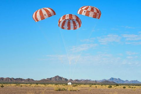 Orion's three main orange and white parachutes help a representative model of the spacecraft descend through sky above Arizona, where NASA engineers tested the parachute system on Sept. 13 at the U.S. Army Proving Ground in Yuma. (NASA/Rad Sinyak)
