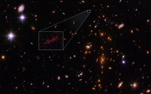 This Hubble Space Telescope image shows the farthest galaxy yet seen in an image that has been stretched and amplified by a phenomenon called gravitational lensing. (NASA , ESA, and B. Salmon (STScI))