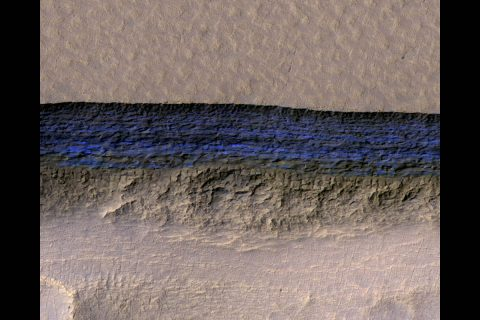 A cross-section of underground ice is exposed at the steep slope that appears bright blue in this enhanced-color view from the HiRISE camera on NASA's Mars Reconnaissance Orbiter. The scene is about 550 yards wide. The scarp drops about 140 yards from the level ground in the upper third of the image. (NASA/JPL-Caltech/UA/USGS)