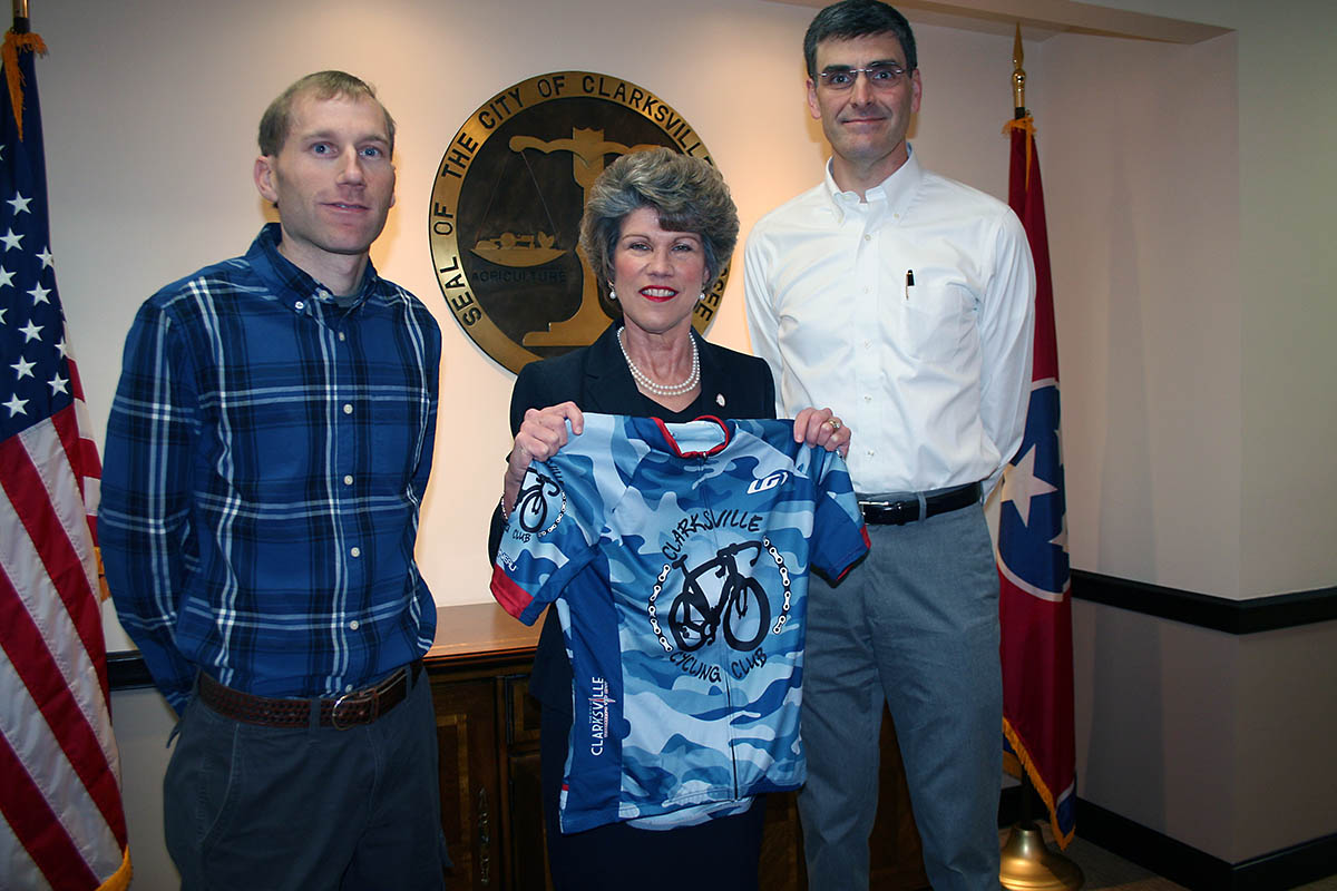 Clarksville Cycling Club members Lawrence Mize and Alex King present Clarksville Mayor Kim McMillan with an official club riding jersey during a recent meeting at City Hall.