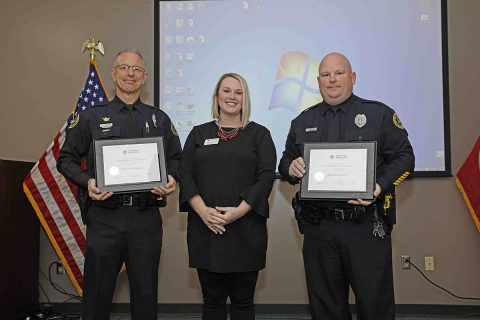 Red Cross' Katy Hagstrom gives Donald Gipson and Darren Koski the Red Cross Extraordinary Personal Action Certificate.