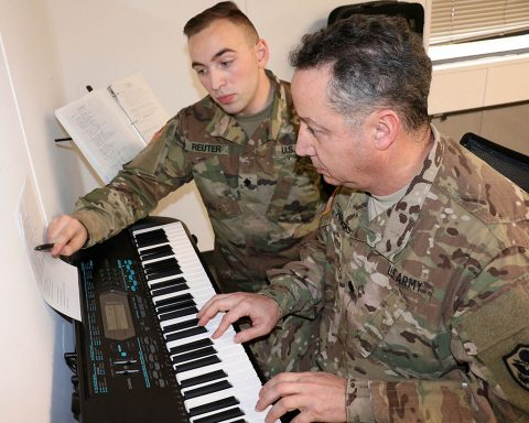 Spc. Walter Reuter, a pianist with the 101st Airborne Division Band, helps Lt. Col. Arnaldo Huertas, a Soldier with the Fort Campbell Warrior Transition Battalion, play through a challenging section of a song during a music lesson, Feb. 1. The battalion's Occupational Therapy department partners with the 101st Airborne Division (Air Assault) Band to provide musical instruction to Soldiers at the WTB. (U.S. Army photo by Maria Yager)