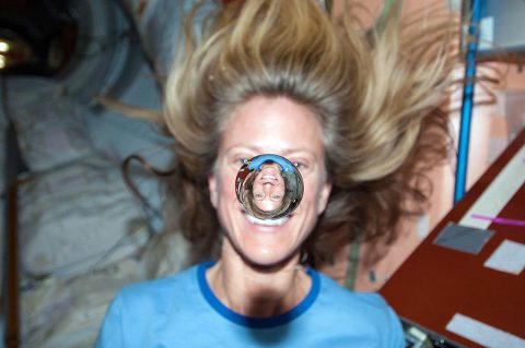 NASA astronaut Karen Nyberg watches a water bubble float freely between her and the camera, showing her image refracted in the droplet. (NASA)