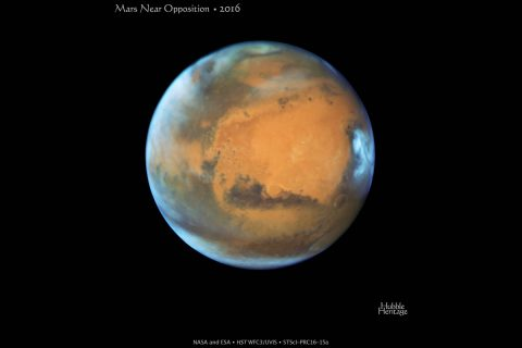 Hydrogen atoms escape from the Mars upper atmosphere, while water containing heavy hydrogen (deuterium) remains trapped on the planet. The escape of hydrogen helped to turn Mars from a wet planet 4.5 billion years ago into a dry world today. (NASA)