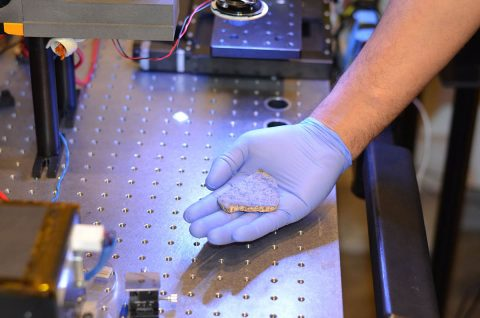 Rohit Bhartia of NASA's Mars 2020 mission holds a slice of a meteorite scientists have determined came from Mars. One of two slices will be used for testing a laser instrument for NASA's Mars 2020 rover while it's still on Earth; the other slice will go to Mars onboard the rover. (NASA/JPL-Caltech)