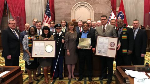 Veteran members of the Tennessee General Assembly pose with Sgt. Walt Peters and the braille American flag