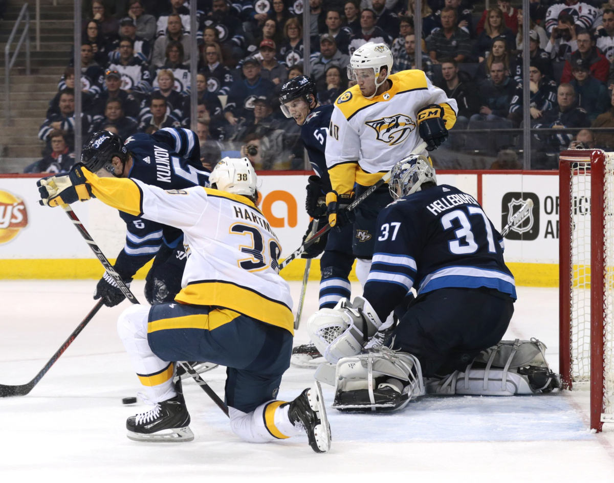 Feb 27, 2018; Winnipeg, Manitoba, CAN; Nashville Predators right wing Ryan Hartman (38) get steady to tip in the game winning goal on Winnipeg Jets goaltender Connor Hellebuyck (37) in the third period at Bell MTS Place. Mandatory Credit: James Carey Lauder-USA TODAY Sports