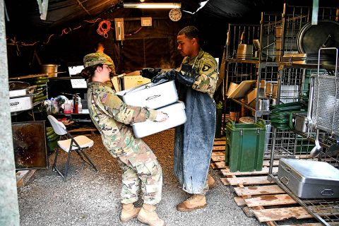 """Pvt. Kaylee Jasper, a food service specialist with E. Company, 6th General Support Battalion, 101st Combat Aviation Brigade, 101st Airborne Division (Air Assault) delivers clean pans to the kitchen February 28, 2018, at Fort Campbell, Ky., during the 50th Annual Phil-lip A. Connelly Competition. """"Just being here helped me learn a lot more than I ever could being in a dining facility,"""" said Jasper. """"This will definitely shape someone and if I re-enlist it will be because of Connelly."""" (Sgt. Marcus Floyd, 101st Combat Aviation Brigade)"""