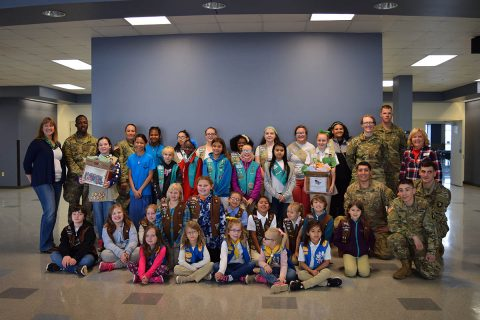 Girl Scouts pose for a group shot with soldiers.