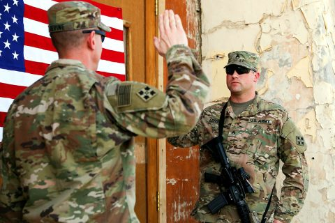 Maj. Patrick Devine (left), chaplain, Train, Advice, Assist Command-South and 2nd Infantry Brigade Combat Team, 4th Infantry Division, officiates the re-enlistment ceremony for Staff Sgt. Marcus P. Levering, religious affairs noncommissioned officer, TAAC-South and 2nd IBCT, 4th Inf. Div., March 17, 2018, in Kandahar, Afghanistan. (U.S. Army photo by Staff Sgt. Neysa Canfield/TAAC-South Public Affairs)