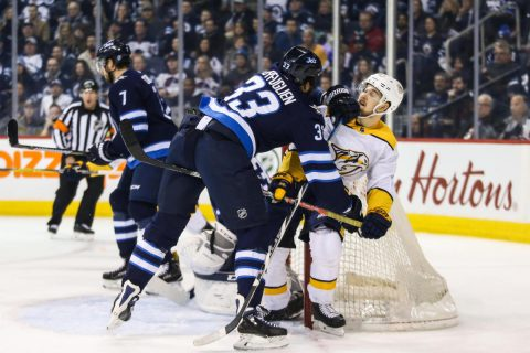 Mar 25, 2018; Winnipeg, Manitoba, CAN; Winnipeg Jets defenseman Dustin Byfuglien (33) checks Nashville Predators forward Viktor Arvidsson (38) during the first period at Bell MTS Place. Mandatory Credit: Terrence Lee-USA TODAY Sports