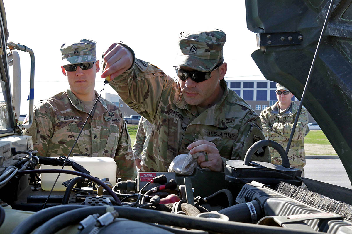 Sgt. Justin Caton, and Sgt. Robert Keys, instructors at The Sabalauski Air Assault School, 101st Airborne Division (Air Assault), perform preventative maintenance checks and services on a high mobility multipurpose wheeled vehicle during the Headquarters and Headquarters Battalion Driver's Training Course test, March 23, 2018, Fort Campbell, Ky. (Pfc. Beverly Roxane Mejia, 40th Public Affairs Detachment)