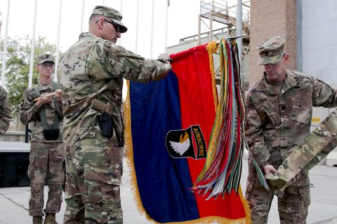 Maj. Gen. Andrew Poppas, 101st Airborne Division (Air Assault) commander, and Command Sgt. Maj. Todd Sims, 101st Abn. Div. senior enlisted leader, unfurl the division headquarters' colors, April 15, during a transfer of authority ceremony at Bagram Airfield, Afghanistan. (Staff Sgt. Lerone Simmons, U.S. Forces Afghanistan)