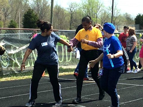 Blanchfield Army Community Hospital Soldier Sgt. Norma Arevalo and Northeast Middle School education assistant Janet Hildebrandt encourage a student-athlete participating in the 100-yard dash at the Special Olympics of Greater Clarksville Spring Games, April 13. (U.S. Army photo by Staff Sgt. Victoria Romero)