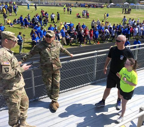 Fort Campbell Warrior Transition Battalion staff, 1st Sgt. Steve Peters and his daughter Abbigail, talk with Soldiers from the Battalion who came out to support Abbigail and other student-competitors from her school at the Special Olympics of Greater Clarksville Spring Games, April 13. Abbigail took first place in the Softball Throw and third place in the 50 meter run. (U.S. Army photo by Sgt. 1st Class Elizabeth Mercedes)