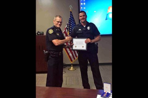 Clarksville Police Chief Al Ansley presents Officer Timothy Simulis with a Lifesaver Award. (CPD)