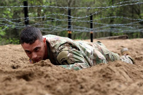 A soldier low crawls under barbed wire at The Sabalauski Air Assault School's on Fort Campbell, KY. (Sgt. Sharifa Newton, 40th Public Affairs Detachment)
