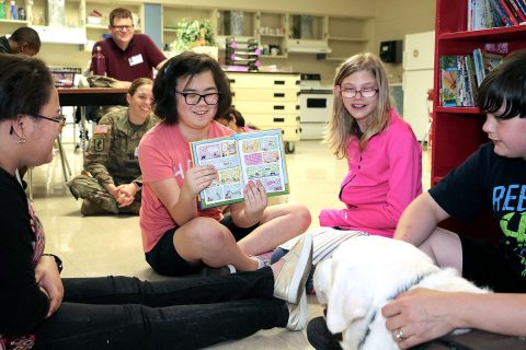 After reading the text, a Northeast Middle School student shows therapy dog Samson pictures from a book. Blanchfield Army Community Hospital pathology technician and animal assisted therapy volunteer Angela Barnett brought her therapy dog Samson to a recent visit with the hospital's Partners in Education school recently. Students took turns reading stories to Samson and learned about the differences between a service dog and a therapy dog. (U.S. Army photo by Maria Yager)
