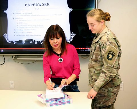 Best-selling author of the What to Expect series, Heidi Murkoff, signs a copy of her book What to Expect When Expecting for Spc. Savannah Tuepker, a participant at an orientation session for active-duty Soldiers at the Women's Health Clinic at Blanchfield Army Community Hospital, April 25th. (U.S. Army photo by Maria Yager)
