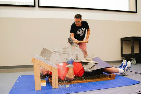 APSU professor of physics Dr. Jaime Taylor has a cinderblock crushed on his chest during the Governor's School for Computational Physics.