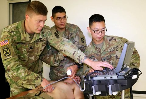 Interservice Physician Assistant Program Phase II student Capt. Dakota Mitchell, assigned to Blanchfield, shows combat medic specialist, Spc. Joshua Huante, assigned to 1st Battalion, 187th Infantry Regiment, 3rd Brigade Combat Team, 101st Airborne Division, and patient administration specialist, Spc. Wooyoung Chun, assigned to 626th Brigade Support Battalion, 3rd Brigade Combat Team, 101st Airborne Division how to operate an ultrasound machine on fellow IPAP Phase II student Capt. Zachary Quigg. (U.S. Army photo by Maria Yager)