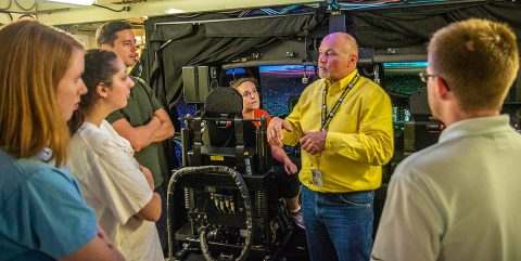 John Kokoski, flight instructor at the Transportable Blackhawk Operations Simulator explains how the TBOS for an UH-60M Black Hawk Multi-Mission Helicopter functions. The TBOS's purpose is to give Army pilots a real time, real feel flying hours and practice their piloting skills before actually taking flight. (Sgt. Steven Lopez, 40th Public Affairs Detachment)