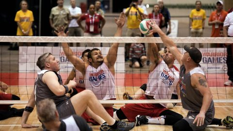SOCOM Maj. Adam Ziegler, left, and SOCOM MSgt. Benjamin Brodt, right, battle Marine Corps veteran LCpl. Matthew Grashen, left center, and LCpl. Michael Sousa Docarmo for the ball during their sitting volleyball game at the 2017 Department of Defense (DoD) Warrior Games in Chicago, Ill., July 1, 2017.  (Roger L. Wollenberg)