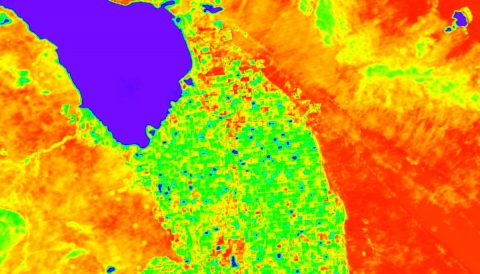 A simulation of ECOSTRESS land surface temperature data around California's Salton Sea (dark blue area, upper left). Cooler areas appear in blue and green, warmer areas are in yellow and red. The region south of the lake that appears green is mostly agricultural fields, and other surrounding areas are desert. (NASA / JPL-Caltech)
