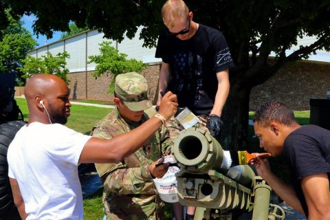 Pfc. Quadry Wilson, Spc. Fenando Carbajal Montes, Spc. Nicholas Johnston and Pvt. Jayson Taylor prime a 105mm M3 Airborne howitzer for repainting, 29 June, at the Don F. Pratt Memorial Museum on Fort Campbell, Kentucky. (Pfc. Lynnwood Thomas, 40th Public Affairs Detachment)